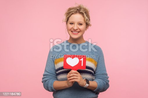 640248524 istock photo Portrait of happy adult woman with curly hair in warm sweater holding heart Like icon, love content 1221184780