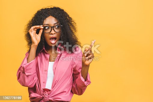Portrait of happy african american black woman indicates with fore finger at blank copy space, shows place for your advertisement or promotional text. Pointing finger