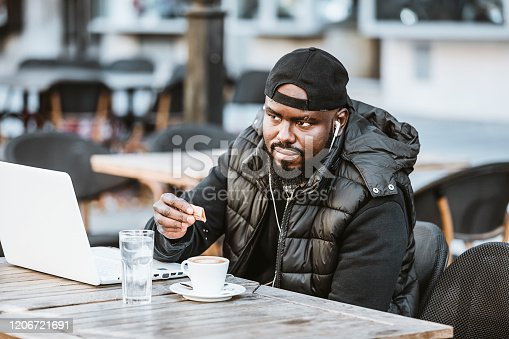 544356862 istock photo Portrait of happy african american man sitting at cafe with laptop computer. Young African American is Enjoying in Coffee in the Outdoor Cafe 1206721691
