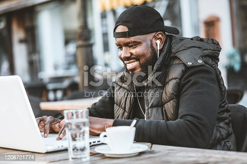 544356862 istock photo Portrait of happy african american man sitting at cafe with laptop computer. Young African American is Enjoying in Coffee in the Outdoor Cafe 1206721774