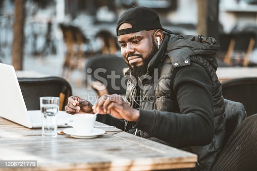 544356862 istock photo Portrait of happy african american man sitting at cafe with laptop computer. Young African American is Enjoying in Coffee in the Outdoor Cafe 1206721779