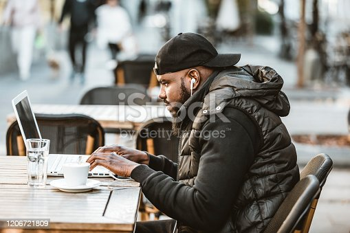 544356862 istock photo Portrait of happy african american man sitting at cafe with laptop computer. Young African American is Enjoying in Coffee in the Outdoor Cafe 1206721809