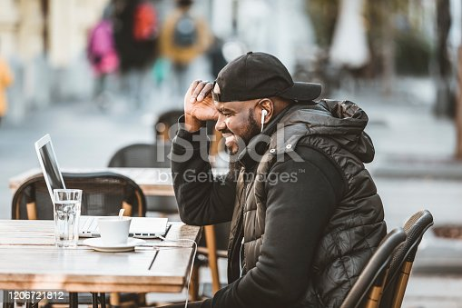 544356862 istock photo Portrait of happy african american man sitting at cafe with laptop computer. Young African American is Enjoying in Coffee in the Outdoor Cafe 1206721812