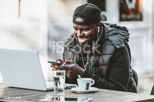 544356862 istock photo Portrait of happy african american man sitting at cafe with laptop computer. Young African American is Enjoying in Coffee in the Outdoor Cafe 1206721845