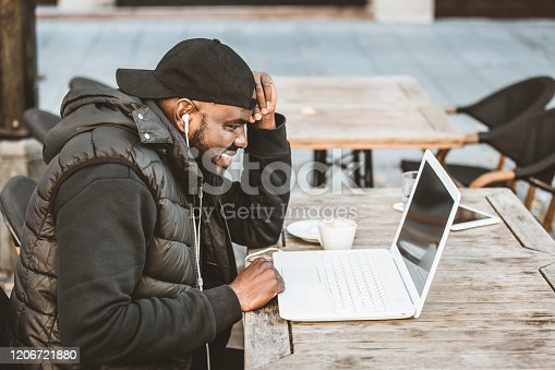 544356862 istock photo Portrait of happy african american man sitting at cafe with laptop computer. Young African American is Enjoying in Coffee in the Outdoor Cafe 1206721880