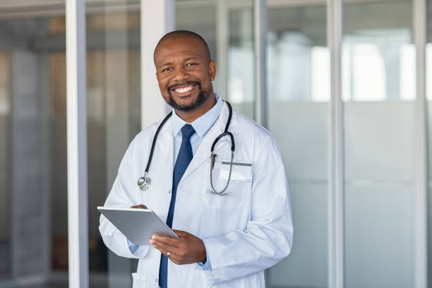 portrait of happy african doctor at private clinic - doctor imagens e fotografias de stock