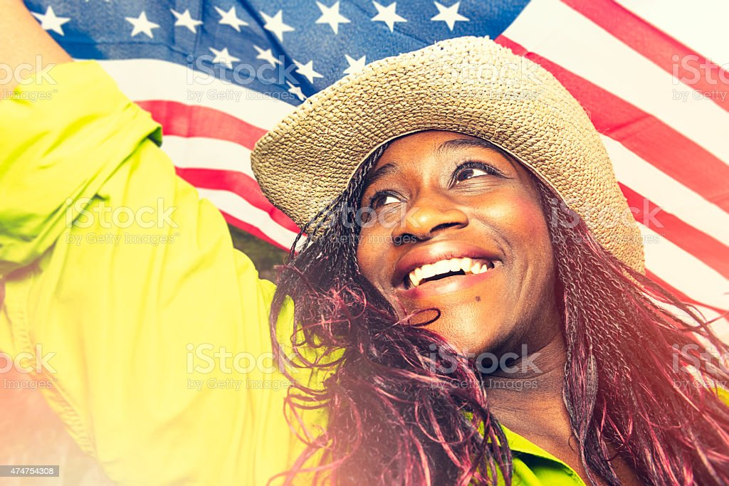 Portrait of happy African young woman under American flag, outdoors.