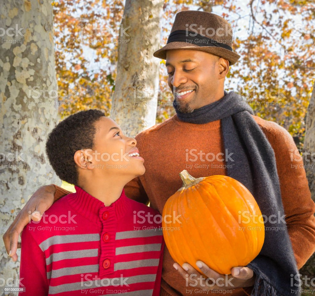 Portrait of happy African-American father and son with pumpkin in Autumn. stock photo