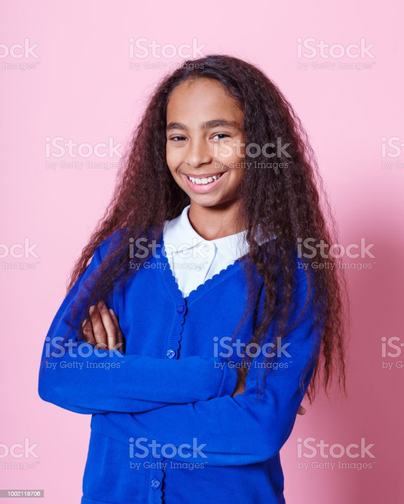 Portrait of happy afro amercian schoolgirl Afro American schoolgirl wearing school uniforms standing with arms crossed and smiling at camera. Studio shot, pink background. 10-11 Years Stock Photo