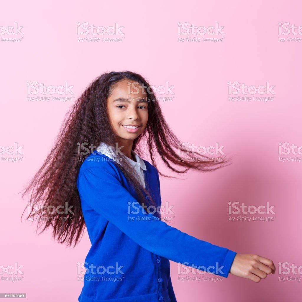 Portrait of happy afro amercian schoolgirl Afro American schoolgirl wearing school uniforms smiling at camera. Studio shot, pink background. 10-11 Years Stock Photo