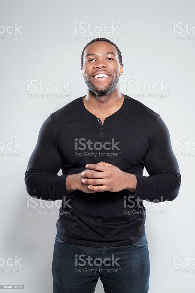 Portrait of happy afro american young man Portrait of happy afro american young man wearing in black, standing against grey background, laughing at camera. Adult Stock Photo