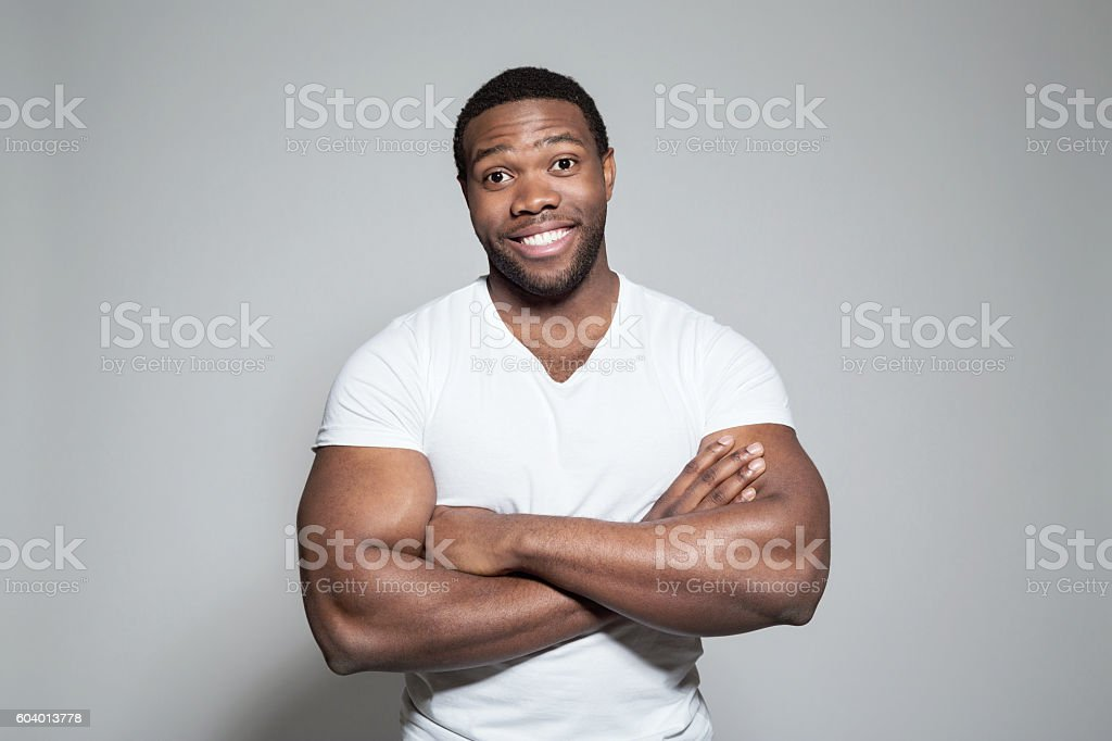 Portrait of happy afro american young man Portrait of happy afro american young man wearing white t-shirt, standing against grey background with arms crossed, laughing at camera. Adult Stock Photo