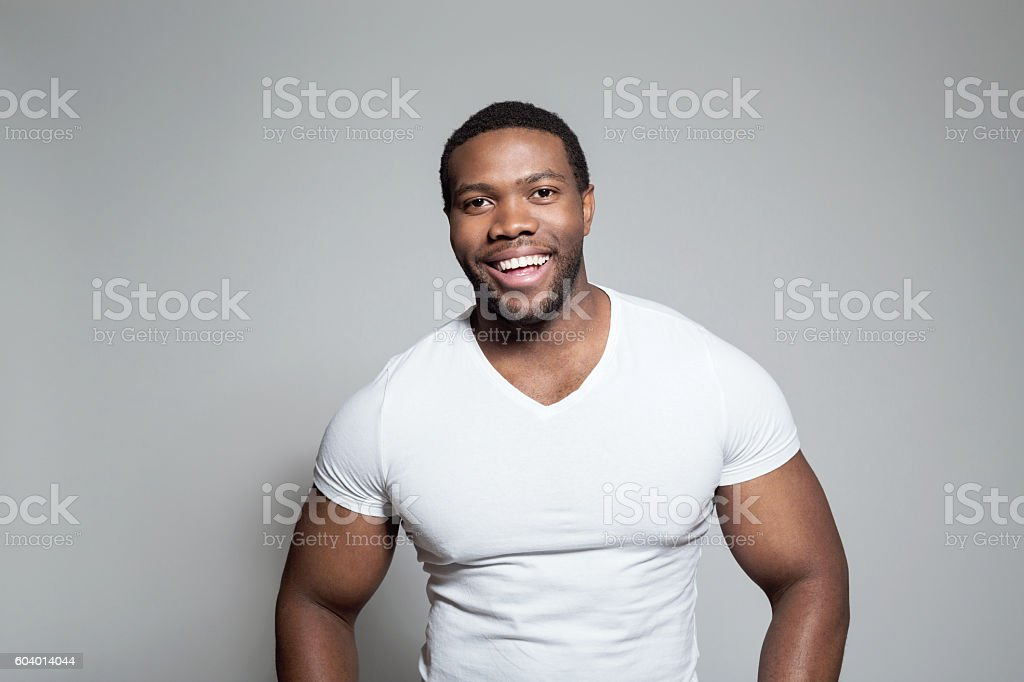Portrait of happy afro american young man Portrait of happy afro american young man wearing white t-shirt, standing against grey background, laughing at camera. Adult Stock Photo