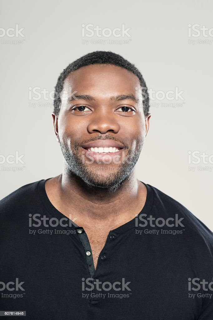 Portrait of happy afro american young man Portrait of happy afro american young man wearing black t-shirt, standing against grey background, smiling at camera. Adult Stock Photo