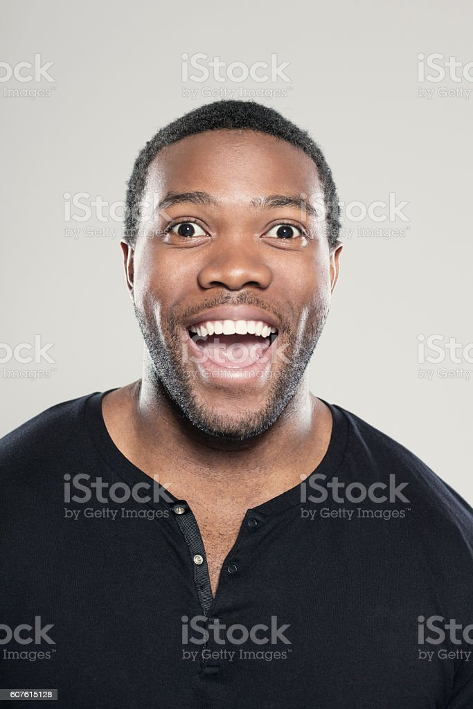 Portrait of happy afro american young man Portrait of happy afro american young man wearing black t-shirt, standing against grey background, laughing at camera. Adult Stock Photo