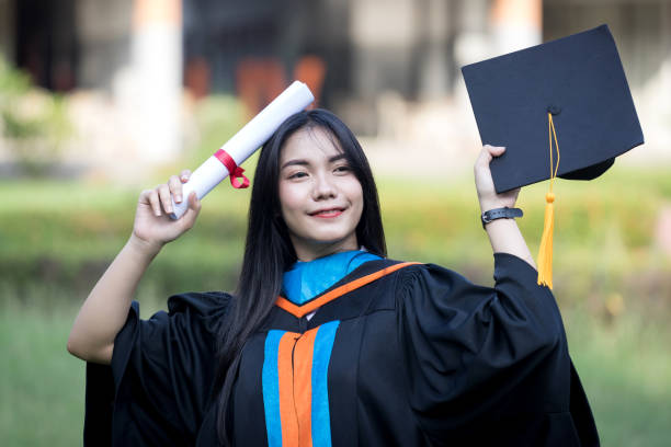 Portrait of happy and excited of young Asian female university graduate wears graduation gown and hat celebrates with degree in university campus in the commencement day. Education concept. stock photo