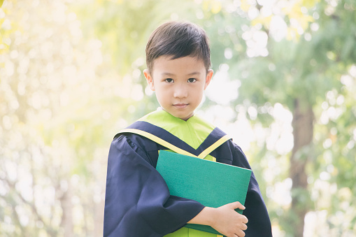 Little boy in graduating clothes on white background