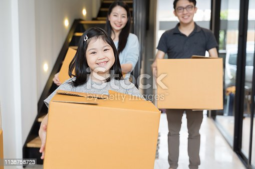 670900812istockphoto Portrait of happy Asian family moving to new house with cardboard boxes. 1138758723