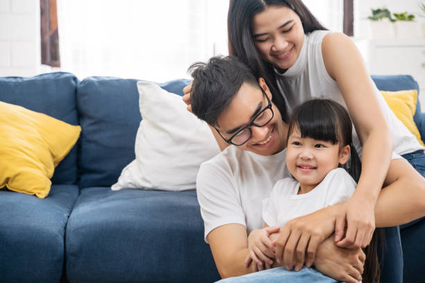 porträt der glücklichen asiatischen familie verbringen zeit zusammen auf dem sofa im wohnzimmer. familien- und wohnkonzept. - asien stock-fotos und bilder
