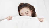 istock Portrait of happy Asian girl looking at camera undercover. Young beautiful Chinese woman waking up at home, smiling while lying in bed. 1181565159