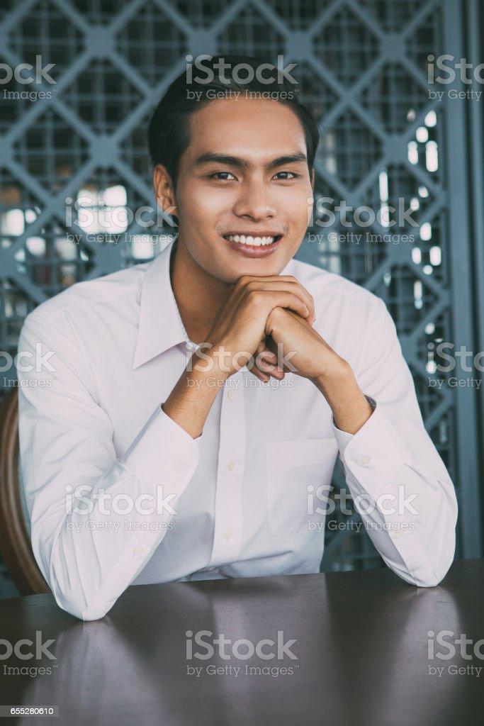Portrait of Happy Asian Man Sitting in Restaurant stock photo