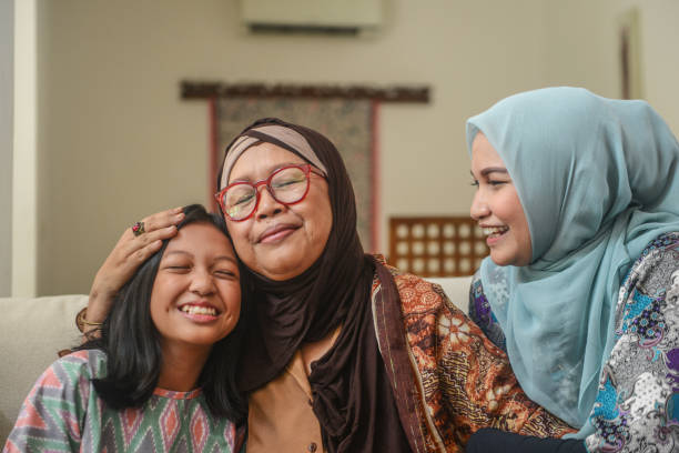 A portrait of happy Asian Muslim young girl with mother and grandmother sitting at home during Hari Raya celebration A portrait of happy Asian Muslim young girl with mother and grandmother sitting at home during Hari Raya celebration indonesian ethnicity stock pictures, royalty-free photos & images