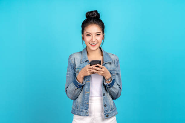 Portrait of Happy asian woman feeling happiness and looking camera holding smartphone on blue background. Cute asia girl smiling wearing casual jeans shirt and connect internet shopping online stock photo