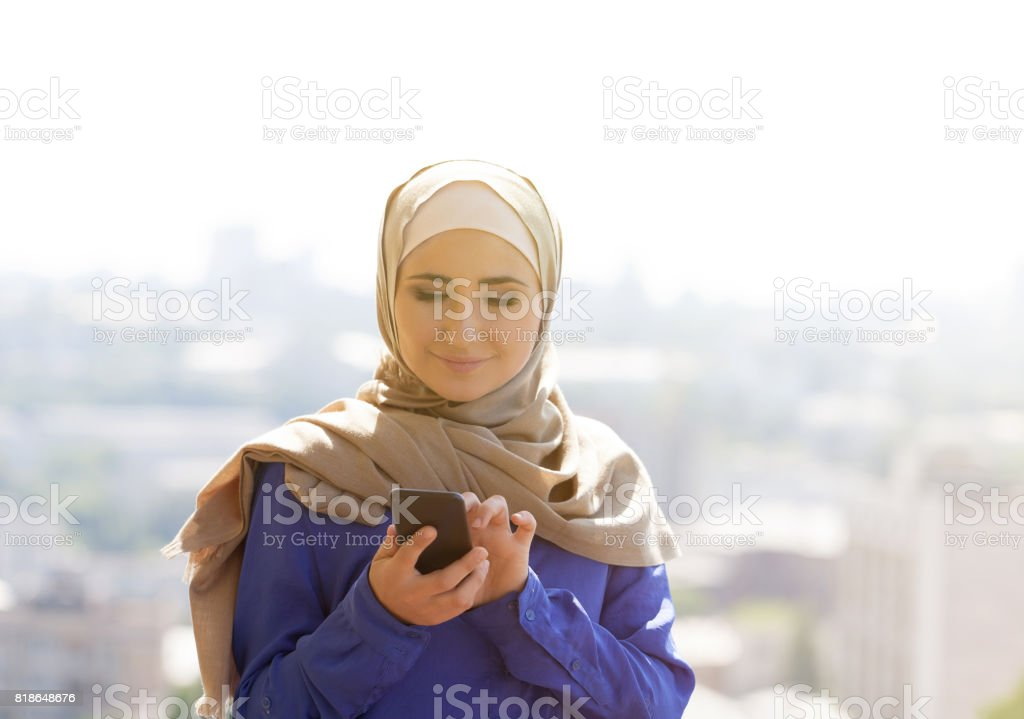 portrait of happy asian woman wearing hijab calling with mobile phone stock photo