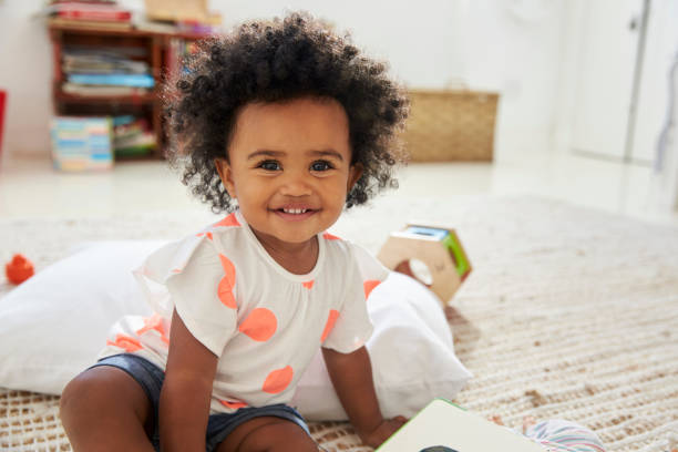 Portrait Of Happy Baby Girl Playing With Toys In Playroom - foto stock