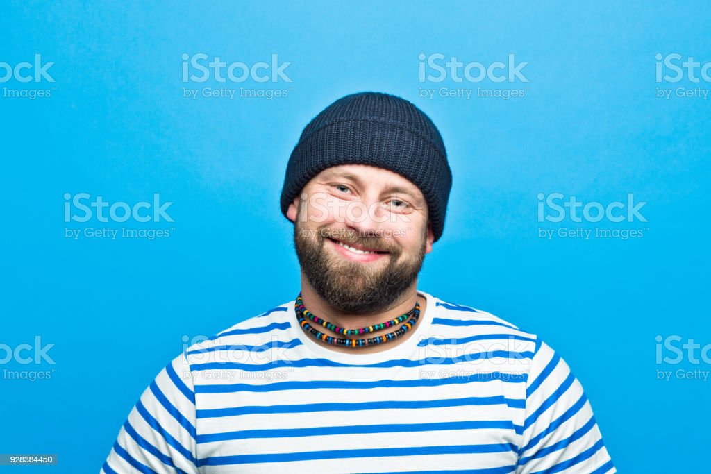 Portrait of happy bearded sailor against ble background Portrait of happy bearded man wearing striped t-shirt and beanie hat smiling at camera. Studio shot, blue background. 30-34 Years Stock Photo