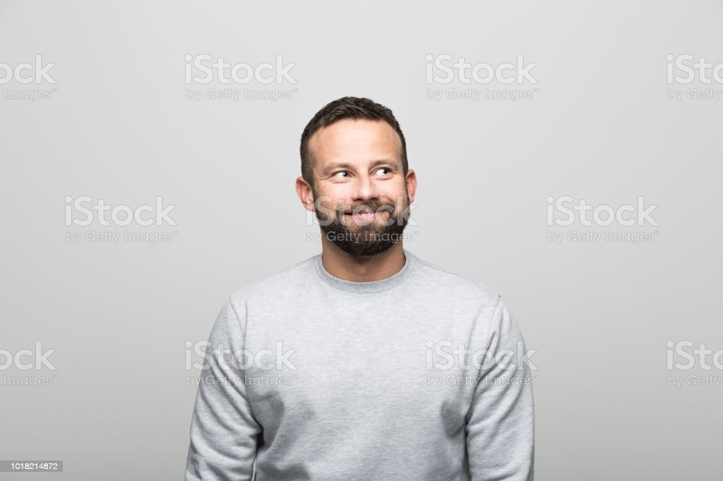 Portrait of happy bearded young man looking away, grey background Portrait of excited bearded young man looking away. Studio shot, grey background. 30-34 Years Stock Photo