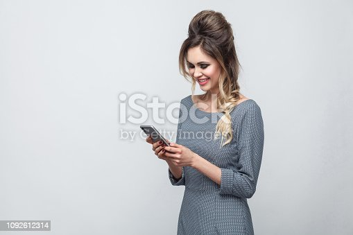 640046924 istock photo Portrait of happy beautiful blogger teenager wearing in grey dress with pigtail on head standing, using smartphone and texting message with toothy smile. 1092612314