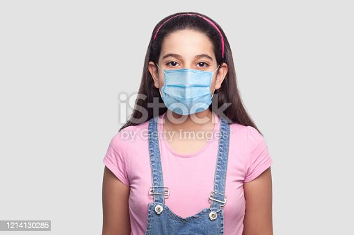 Portrait of girl with medical mask in casual style, pink t-shirt and blue denim overalls standing and looking. indoor studio shot, isolated on gray background.