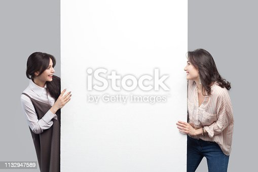 933380808 istock photo Portrait of happy beautiful brunette young women in casual style standing near empty white blank copyspace and looking at each other with toothy smile. 1132947589