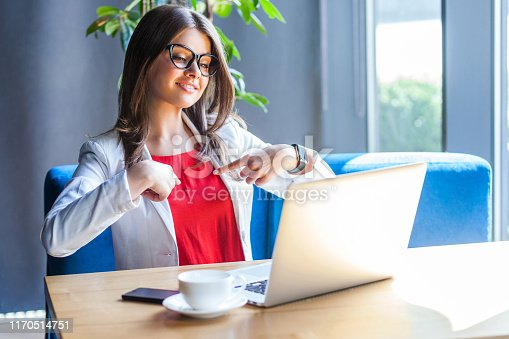 Portrait of happy beautiful stylish brunette young woman in glasses sitting, looking at her laptop screen on video call, pointing herself and toothy smile. indoor studio shot, cafe, office background.