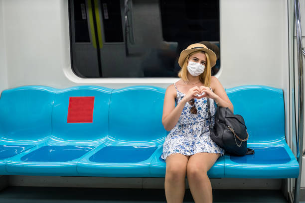 Cтоковое фото Portrait of happy beautiful woman with surgical medical mask and with love heart gesture while smiling