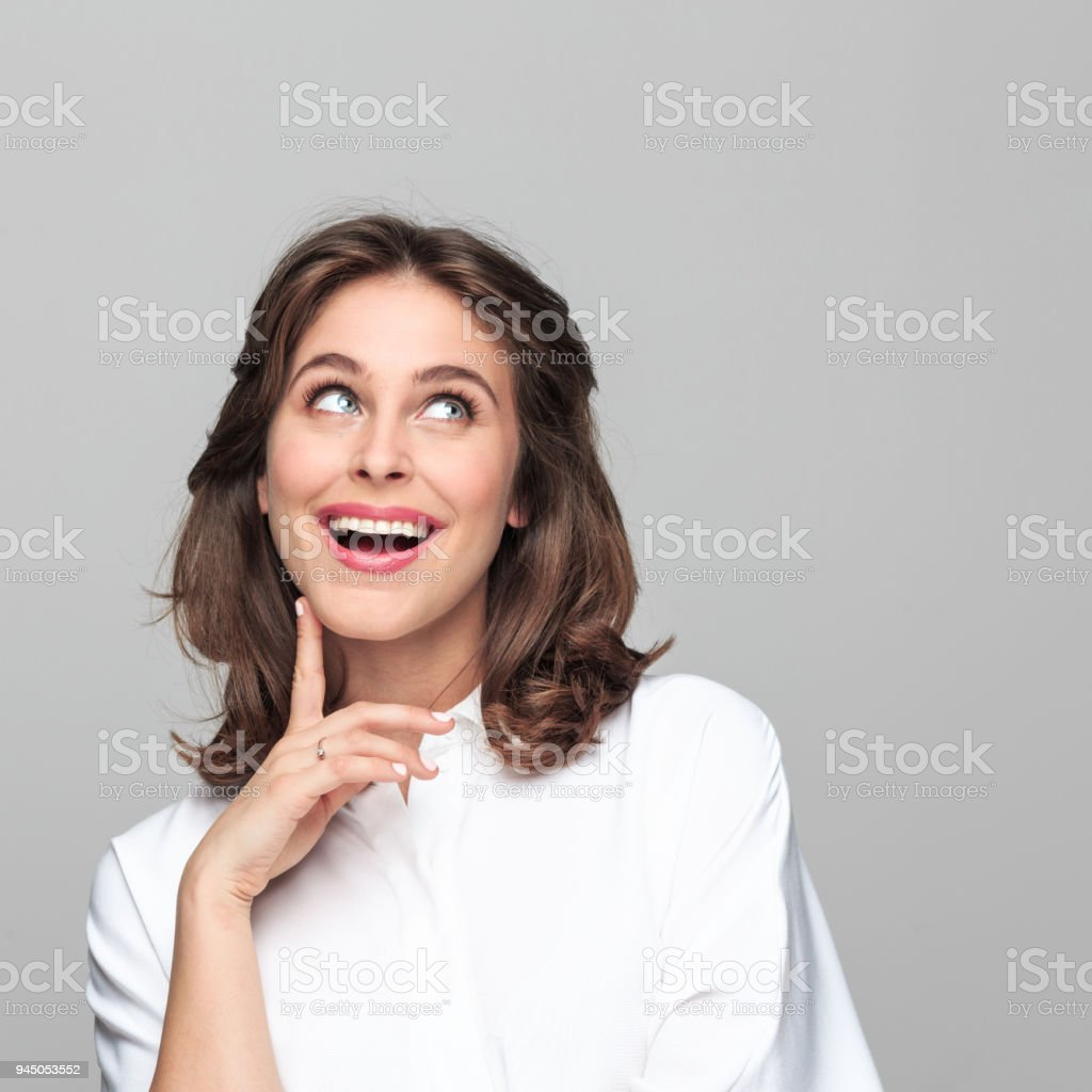 Portrait of happy beautiful young businesswoman Portrait of happy, beautiful young businesswoman looking up with hand on chin against grey background. 25-29 Years Stock Photo