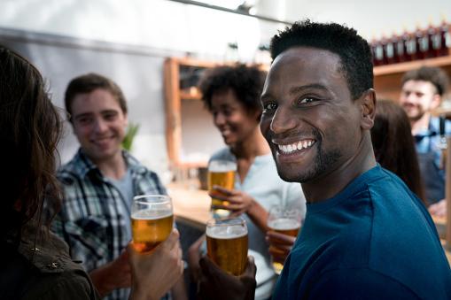 Foto de Retrato De Homem Negro Feliz Bebendo Cerveja Com Amigos Olhando  Para A Câmera Sorrindo e mais fotos de stock de 20 Anos - iStock
