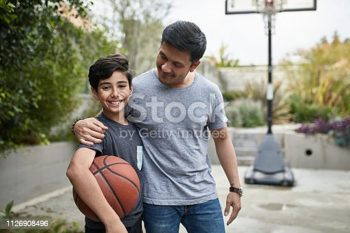 Portrait of happy boy and father with basketball