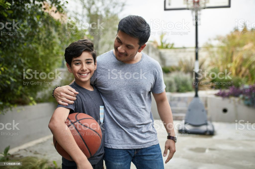 Portrait of happy boy and father with basketball stock photo