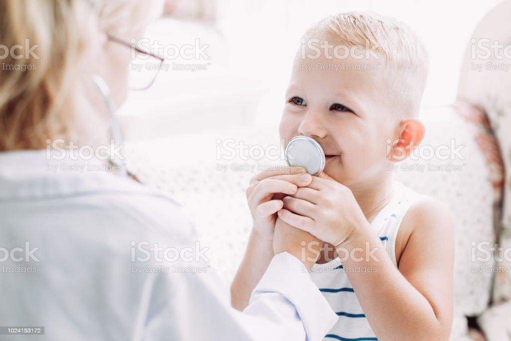 Portrait of happy boy breathing at stethoscope stock photo
