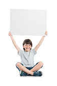 Smiling little boy holding placard isolated on white background. Happy cute boy holding blank poster sitting on white floor. Laughing child showing empty white sign.