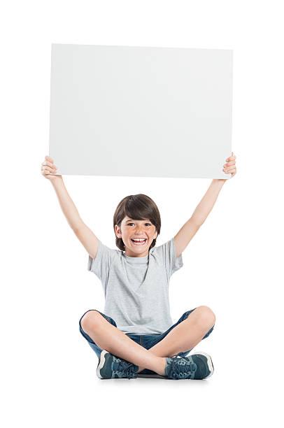 porträt von happy boy holding sign - sprüche kinderlachen stock-fotos und bilder