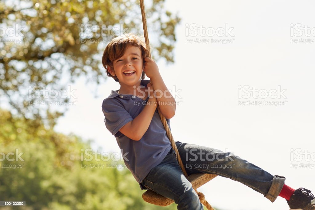 Portrait of happy boy playing on swing against sky stock photo