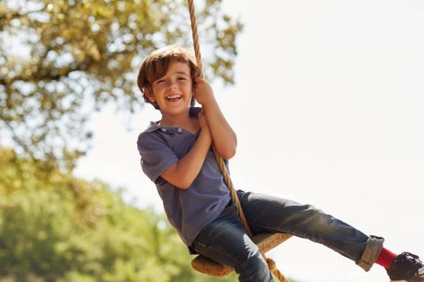 portrait of happy boy playing on swing against sky - balouço imagens e fotografias de stock