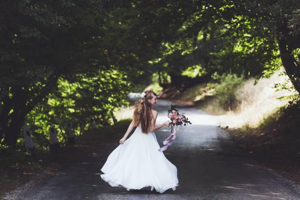 porträt der glückliche braut auf landstraße im sommer. hochzeit-bouquet mit seidenbänder. sie wirbelt im tanz - hipster braut stock-fotos und bilder