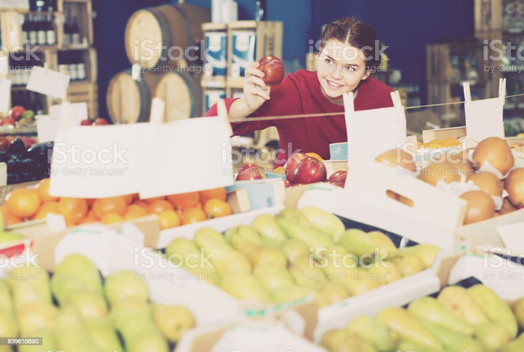 Portrait of happy brunette girl buying apple in supermarket stock photo