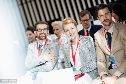 istock Portrait of happy business people sitting in seminar hall 616131836