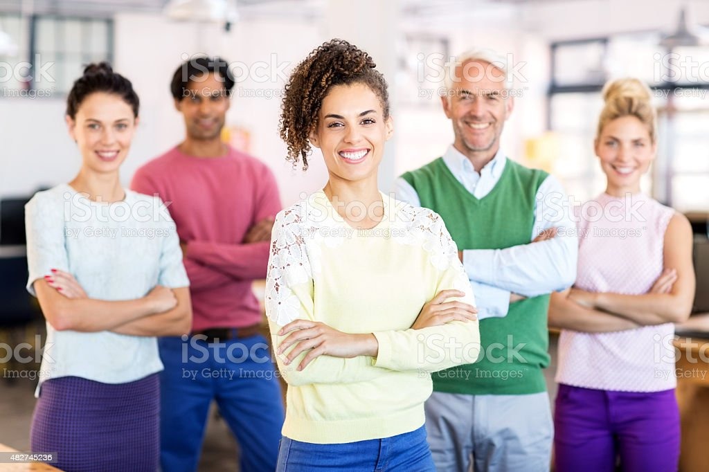 Group portrait of happy business team standing arms crossed in...