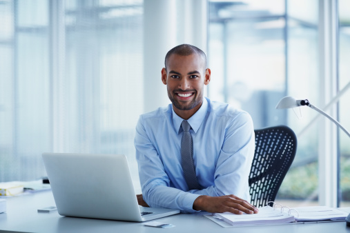 Portrait of happy businessman sitting with laptop at desk in office